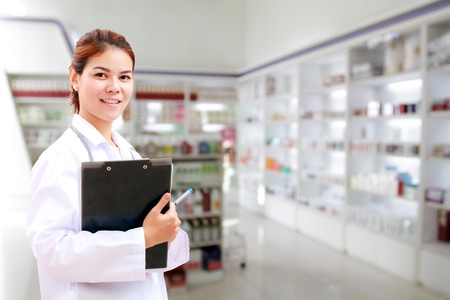 medicine cabinet: pharmacist chemist and medical doctor woman asia with stethoscope and clipboard checking medicine cabinet and pharmacy drugstore Stock Photo
