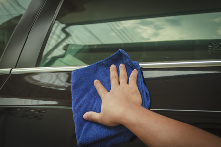 microfiber: Hand with microfiber cloth cleaning black car.