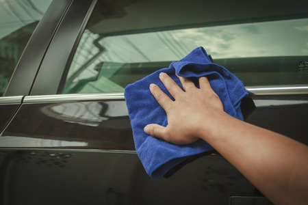 microfiber cloth: Hand with microfiber cloth cleaning black car.