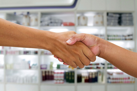 deal in: handshake in a business and deal in the pharmacy background Stock Photo