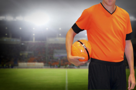 football player holding ball on football stadium background