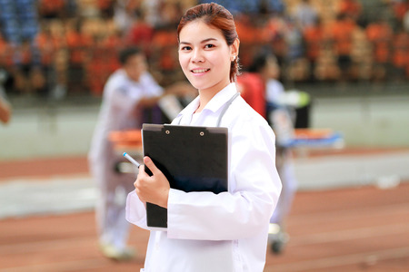 hospital trolley: Smiling medical doctor woman Asia with stethoscope on injured player at the football match and on Stretcher and hospital trolley background