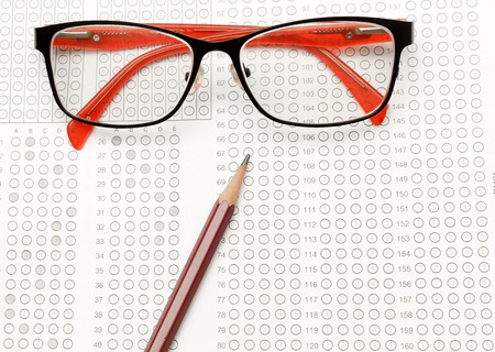 standardized: glasses and pencil on Standardized test form with answers bubbled in and a pencil, focus on anser sheet