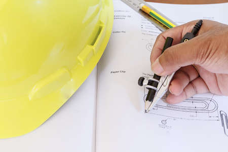 hard hat with pencil compasses and rulersbook on table and wall Stock Photo