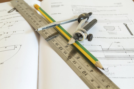 depth measurement: pencil with compasses and rulers on wood table