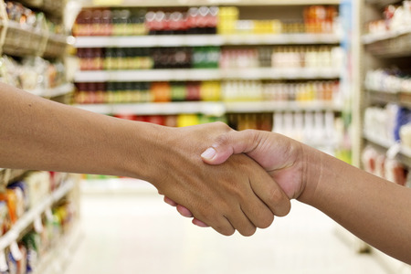 deal in: handshake in a business and deal in the  supermarketmall for background. Stock Photo