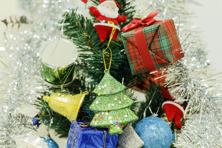 Happy new year and Christmas ornaments on the Christmas tree with gift box and Christmas background.