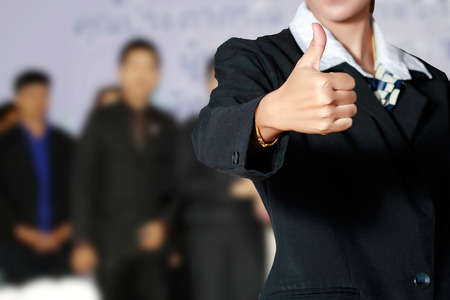 thump: Business woman and business people thump up hand sign on business people background. Stock Photo