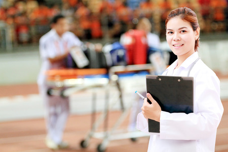 hospital trolley: Smiling medical doctor woman Asia with stethoscope on injured player at the football match and on Stretcher and hospital trolley background. Stock Photo