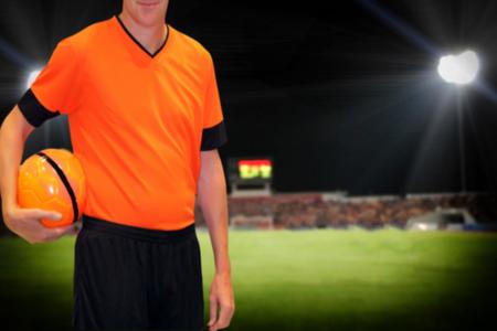 football player holding ball on football stadium background. Stock Photo