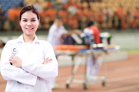 Smiling medical doctor woman Asia with stethoscope on injured player at the football match and on Stretcher and hospital trolley background. Stock Photo