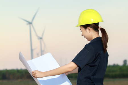 portrait women asia engineer working and holding blueprints at wind turbine farm Power Generator Station Stock Photo