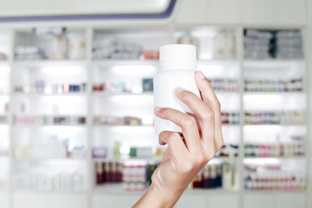 medicine cabinet: hand of doctor holding medicine bottle on medicine cabinet and store medicine and pharmacy drugstore
