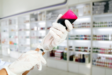 medicine cabinet: Medical gloved hand holding syringe with red blood liquid and a bead of liquid emerging testing the function of the syringe on medicine cabinet and store medicine and pharmacy drugstore