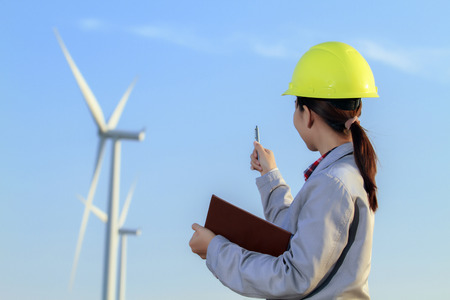 portrait women asia engineer working and holding blueprints at wind turbine farm Power Generator Station Фото со стока