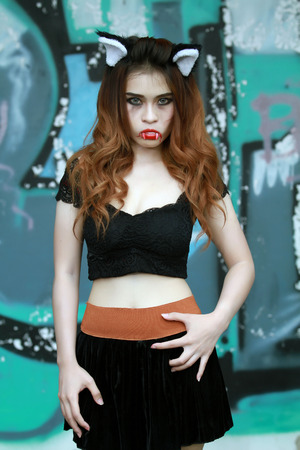 Beautiful Young woman as sexy vampire - halloween portrait on dark background Stock Photo