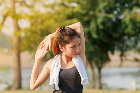 Athletic woman asia warming up and Young female athlete sitting on an exercising and stretching in a park before Runner outdoors, healthy lifestyle concept Stock Photo