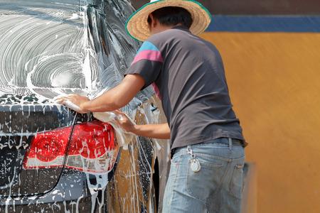 Man asian washing the car using the yellow sponge with foam