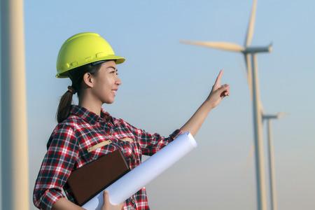 portrait women asia engineer working and holding blueprints at wind turbine farm Power Generator Station Stock Photo