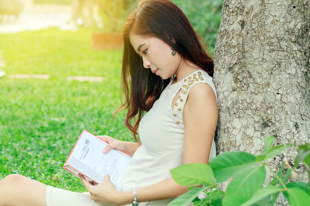 Asian woman reading a book in the garden for relaxation .