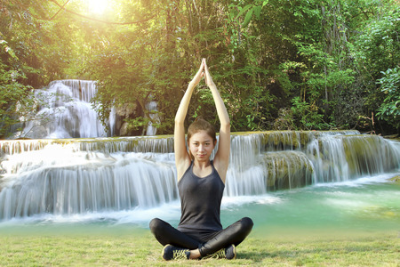 jungle gyms: Blurry and soft focus of Athletic woman asia warming up and Young female athlete sitting and yoga on an exercising and stretching in a Waterfall on sunlight , healthy lifestyle concept Stock Photo