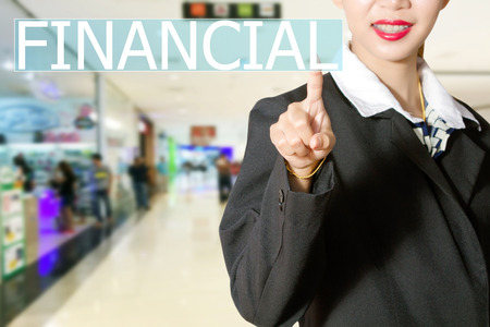 virtual assistant: Businesswomen hand touching FINANCIAL sign on virtual screen on people Business background