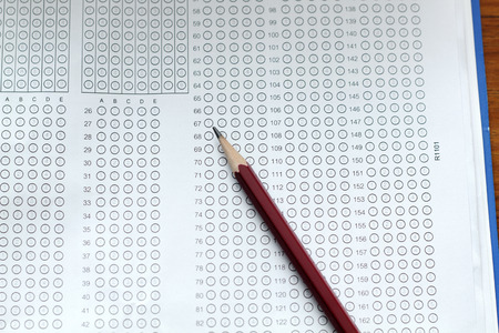 standardized: glasses and pencil on Standardized test form with answers bubbled in and a pencil, focus on answer sheet