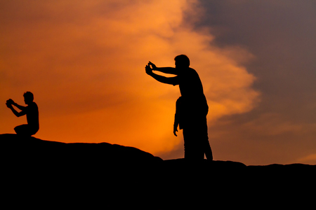 Man silhouette photography and selfie with mountain at sunset .