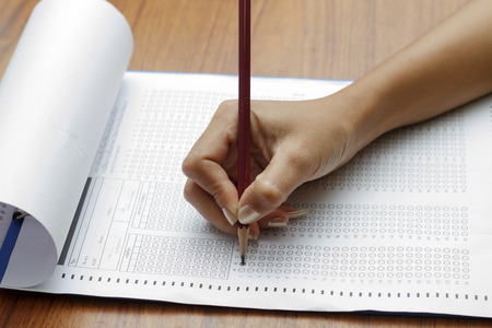 standardized: hand of women holding pencil on Standardized test form with answers bubbled in and a pencil, focus on answer sheet