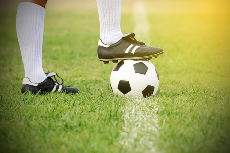 soccer or football player standing with ball on the field for Kick the soccer ball Фото со стока