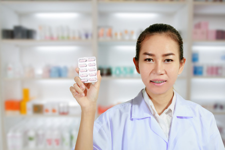 medicine cabinet: Pharmacist and Doctor woman holding pill in hand , health care and pharmacology concept on medicine cabinet and store medicine and pharmacy drugstore for background
