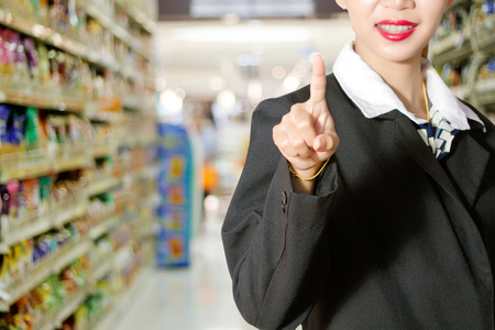 Business women pushing on a touch screen interface in supermarket in blurry Stock Photo