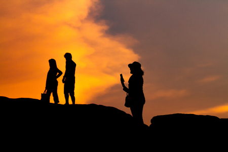 smart woman: women silhouette photography and selfie with mountain at sunset . Stock Photo