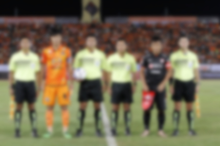 sportsmanship: blurry referee with captain team and opponent team players on football stadium