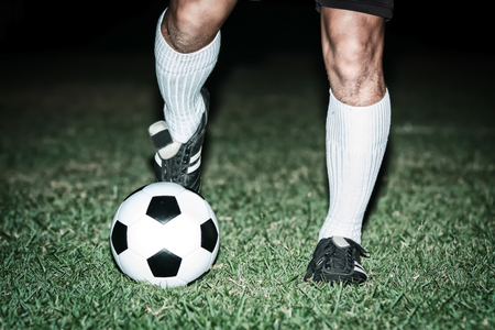 Football player shoot a soccer ball with his feet on the football field on night