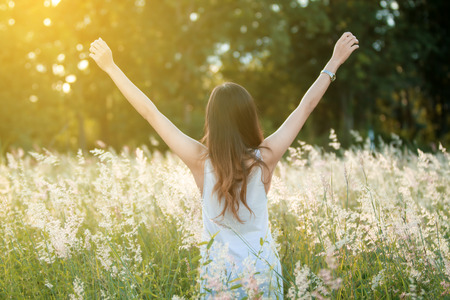 arms above head: Successful woman with arms up and Happy celebrating winning success woman at sunset or sunrise standing elated with arms raised up above her head in celebration
