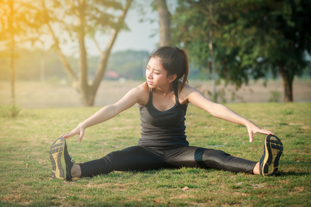 Athletic woman asian warming up and Young female athlete sitting on an exercising and stretching in a park before Runner outdoors, healthy lifestyle concept,blurry and soft focus Stock Photo