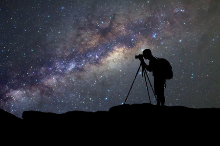 silhouette  of man photography take a photo of Milky Way galaxy on dark night at thailand