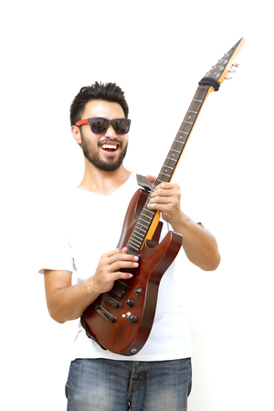 Asian handsome man with a mustache, smiling and laughing and playing guitar and listen music with headphones ,Blurry and soft focus Фото со стока