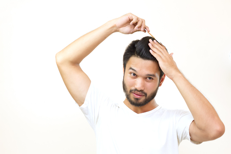 comb: people concept - smiling young man brushing hair with comb on white background,soft focus Stock Photo