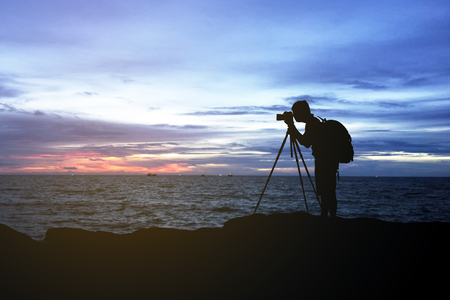 silhouette  of man photography on mountain and sea at sunset Stock Photo