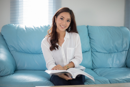Asian women smiling and reading a book for relaxation