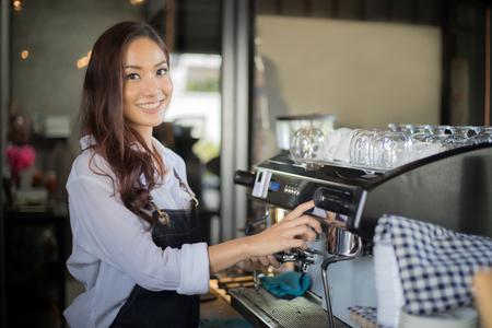 아시아 여성 미소 하 고 커피가 게 카운터 - 작업 여자 중소 기업 소유자 음식과 음료 카페 개념에서에서 바리 스타를 사용 하여 바리 스타