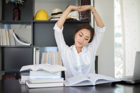 Asian woman stretching at her workplace and smiling in the office