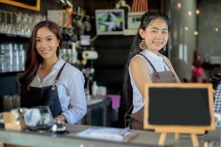 Asian women Barista smiling and using coffee machine in coffee shop counter - Working woman small business owner food and drink cafe concept Фото со стока