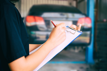 Portrait of smiling young female mechanic inspecting on a car in auto repair shop