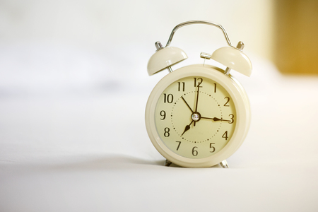 Analog alarm clock on white bed, time in the mornign with a bright sunshine