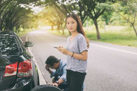 Asian woman using mobile phone while looking and Stressed man sitting after a car breakdown on street Stock Photo