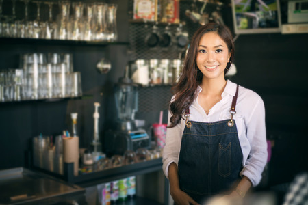 Asian women Barista smiling and using coffee machine in coffee shop counter - Working woman small business owner food and drink cafe concept 스톡 콘텐츠