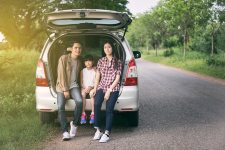 happy little girl  with asian family sitting in the car for enjoying road trip and summer vacation